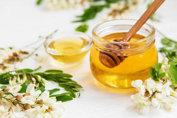 Egy fehér asztalon üvegben és egy kis tálban méz és mézcsurgató, mellettük akácvirágok.