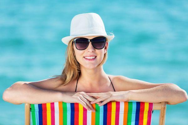 Strandon egy nyugágyban fiatal lány fürdőruhában, napszemüvegben és sapkában mosolyog.