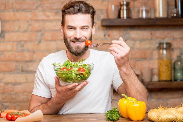 Egy konyhában fiatal férfi zöld leveles zöldségeket és paradicsomot tartalmazó salátás tálat tart a kezében.