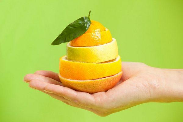 Egy zöld háttér előtt egy kéz felszeletelt narancsot tart.