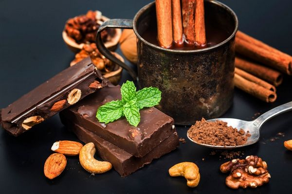 Egy sötét színű asztalon étcsokoládé, mogyoróscsoki, fahéjrudak, kanálban kakaópor, mellettük mandulák, diók, kesudiók.