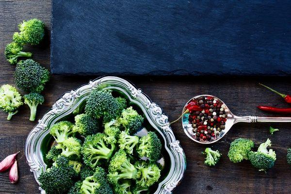 Egy asztalon egy ezüst tálcán és mellette brokkoli és kanálban színes bors.