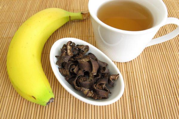 Egy asztalon babuszon banán, egy tálban szárított banánhéj, mellettük egy csészében banántea,