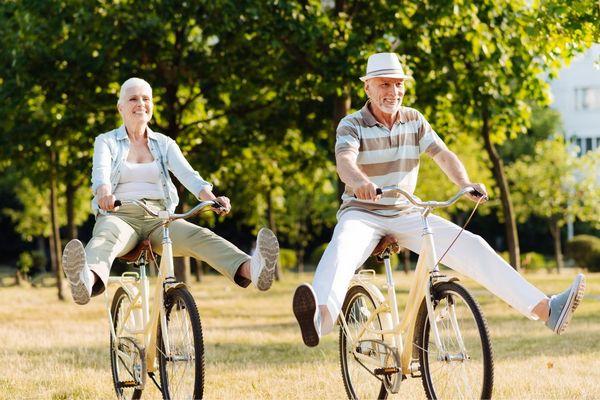 Kint a szabadban egy idős házaspár nevetve biciklizik, lábaikat felemelik közben.