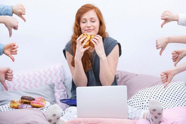 Egy fiatal lány egy kanapén ülve két kezében és mellette egy tányéron fánkok, melyeket a szájához emel, két oldalról dislike-t mutató kezek.