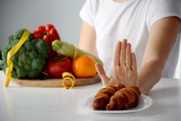 Egy asztalon egy tálban egészséges zöldségek, brokkoli, paprika, paradicsom, cukkini, mellette egy tányéron croissan, amit egy hölgy kezével elutasít.