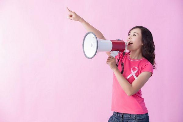 Egy rózsaszínű háttér előtt fiatal lány ciklámen színű pólóban rózsaszínű szalaggal a mellén, kezében hangszóróval felfelé mutat és kiált.