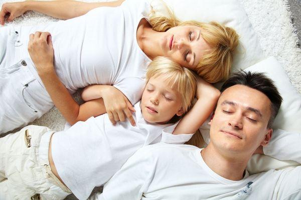 Egy ágyon egy család alszik, anya, apa és a kisfiúk.
