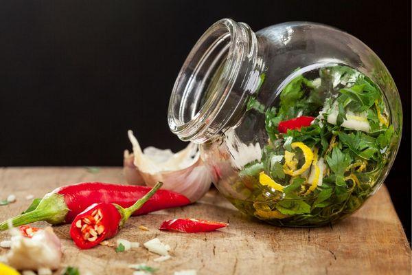 Egy asztalon üvegben fűszerek, oregánó, bazsalikom, citromhéj, mellette chili, fokhagymagerezdek,