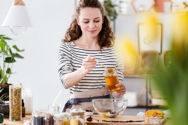 Egy fiatal nő a konyhában mézet kanalaz egy tálba.