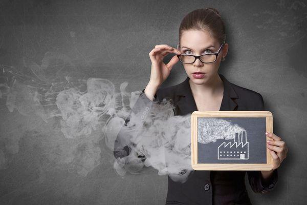 Egy szürke háttér előtt fekete kosztümben fiatal nő, jobb kezével lehúzza a szemüvegét, bal kezében táblát tart, amelyen egy füstölgő gyár képe, amiből nagy füst száll fel.