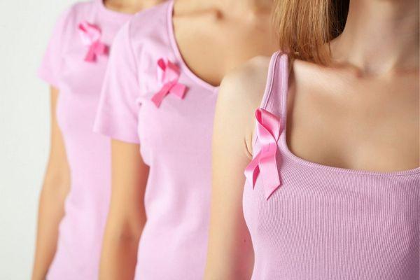 Három hölgy rózsaszínű pólóban egymás mögött áll, mindegyik jobb vállánál a mellrák emblémája, egy rózsaszínű szalag.
