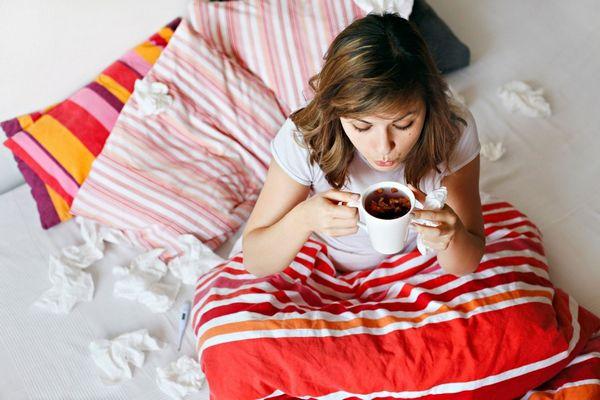 Egy fiatal nő az ágyában ül, piros-fehér csíkos ágyneművel betakarva, gyógyteát kortyolgat.