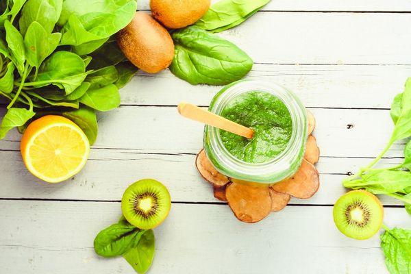Egy asztalon spenótlevelek, kivi, citrom, és egy üvegben zöld smoothie.