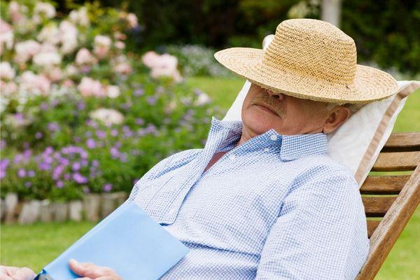 Egy kertben egy idősebb férfi egy nyugágyban szundikál, szalmakalapja az arcára csúszott.