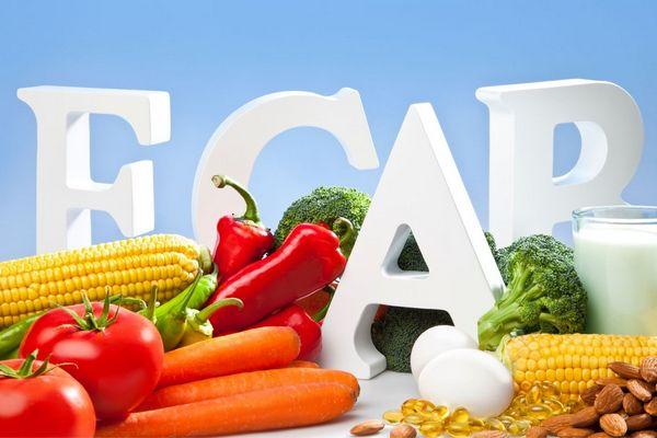 Gyulladást csökkentő vitaminok betűi, E-, C-A-B-vitaminok, mellettük egészséges zöldségek, kukorica, paradicsom, paprika, brokkoli, mandula, tojások, tej egy pohárban.