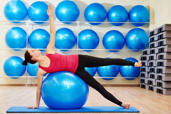 Egy tornateremben kék fitneszlabdák a falra rögzítve, fiatal lány kék fitneszlabdával tornázik.