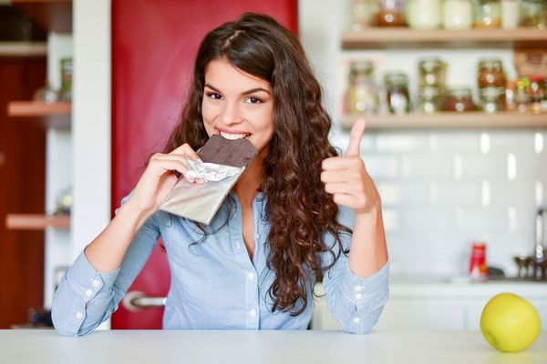Egy fiatal lány a konyhájában ül, egy egész tábla csokoládét tart a kezében, miközben beleharap