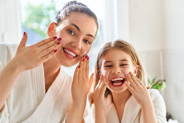 Egy fürdőszobában az anya és a lánya az arcukat krémmel bekeni, miközben nevetnek.