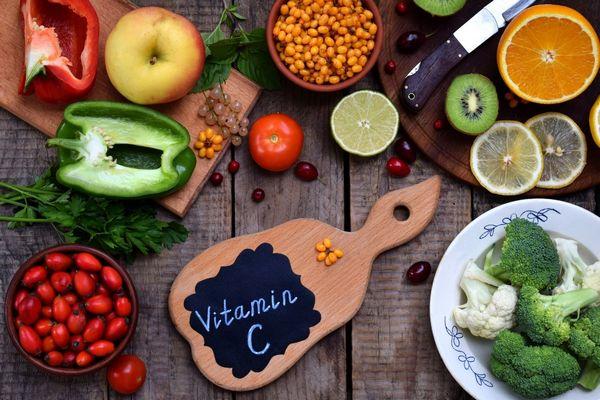 Egy asztalon C-vitamint tartalmazó élelmiszerek, paradicsom, paprika, alma, brokkoli, karfiol, narancs, citrom, kivi, ribizli, spenótlevelek, homoktövis, petrezselyemzöld.