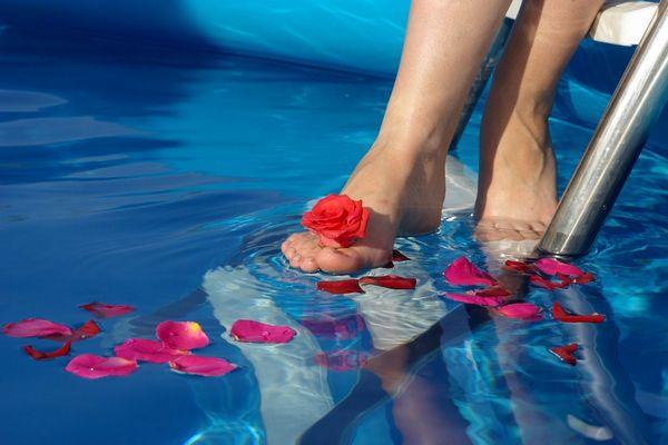 Egy medencében rózsaszirmok, egy lány belelép a vízbe.