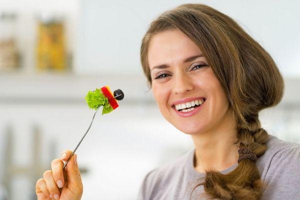 Egy fiatal nő mosolyog, miközben a kezében egy villát tart, amelyen saláta, paprika és olivabogyó van felszúrva.