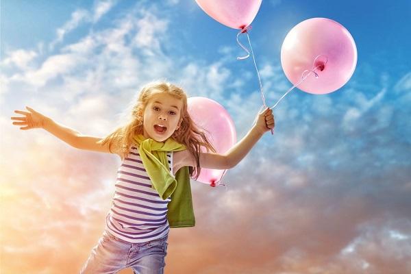 Egy kislány kint a szabadban rózsaszínű léggömböket tart a kezében, miközben szalad.