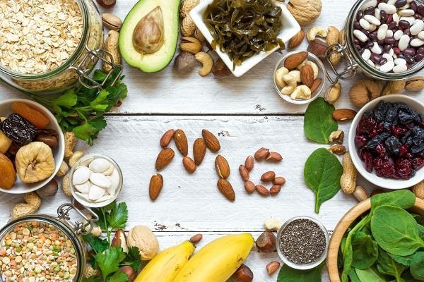 Egy asztalon magnéziumot tartalmazó élelmiszerek, tálakban müzli, lencse, mák, aszalt gyümölcsök, bab, mandula, spenótlevelek, avokádó, banán.