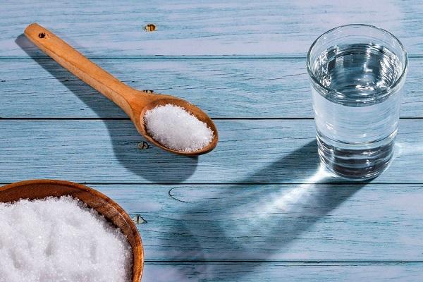 Egy asztalon egy tálban és egy fakanálban pikkelysömör kezelésére való Epsom-só, mellette egy pohár víz.