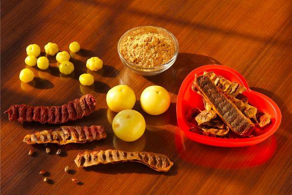 Egy asztalon shikakaipor egy kis tálban, mellette shikakaimagok és shikakai gyümölcsök.