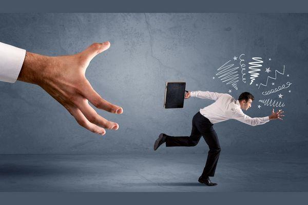 Egy szürke háttér előtt egy stresszes férfi fut, mögötte egy nagy kéz utána nyúl.