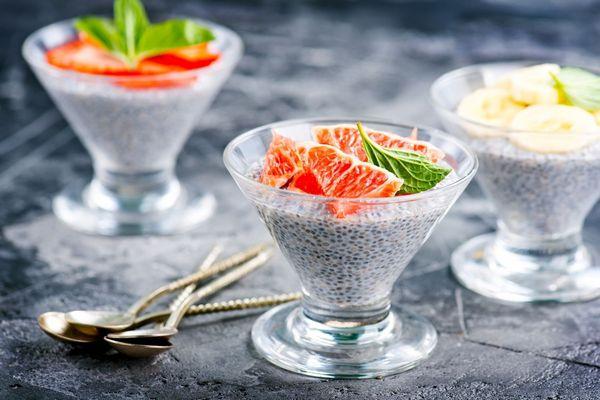 Egy szürke asztalon három üvegpohárban chiamagból készült puding gyümölcsökkel.