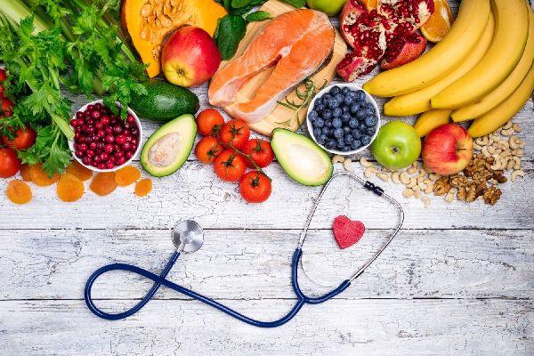 Egy asztalon egészséges táplálékok, banán, lazac, avokádó, sárgarépa, alma, áfonya, paradicsom, gránátalma, sütőtök, magvak és egy fonendoszkóp.