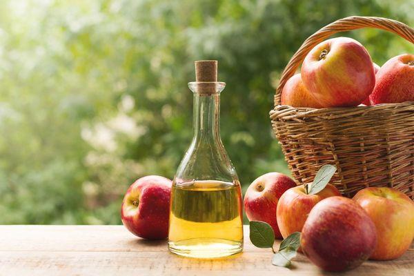 Egy asztalon egy kosárban és mellette almák és üvegben almaecet.