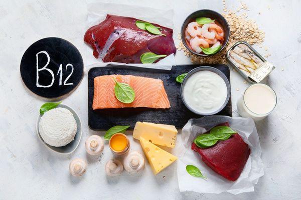 Egy asztalon B12-vitamint tartalmazó tápanyagok, sajtok, gomba, lazac, máj, rák, szardínia, spenót, tej.