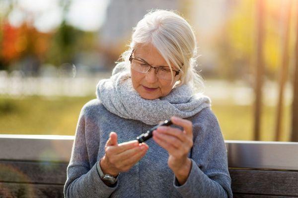 Egy ősz hajú nyugdíjas korú hölgy egy padon ülve az ujjából a vércukorszintjét ellenőrzi.