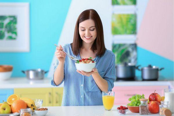 Egy színes konyhában fiatal lány gyümölcsös zabpelyhet kanalazgat.