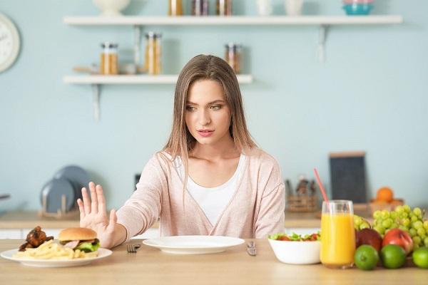Egy fiatal lány az asztalánál ül, előtte egészséges és hormonműködést zavaró táplálékok, ez utóbbi felé elutasítóan mutat.