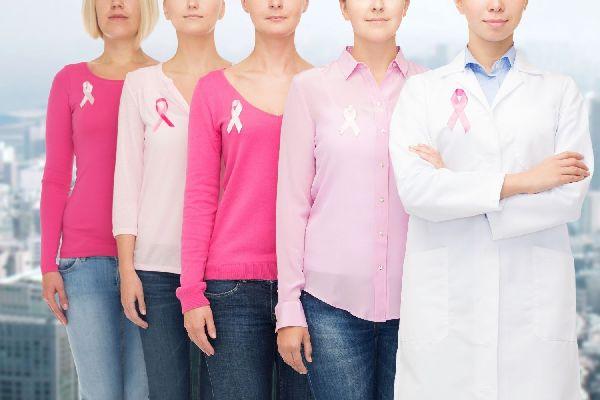 Az utcán négy nő egymás mögött áll rózsaszínű pólóban, jobb válluknál rózsaszínű szalaggal, a mellrák szimbólumával, előttük egy fehér köpenyes nő.