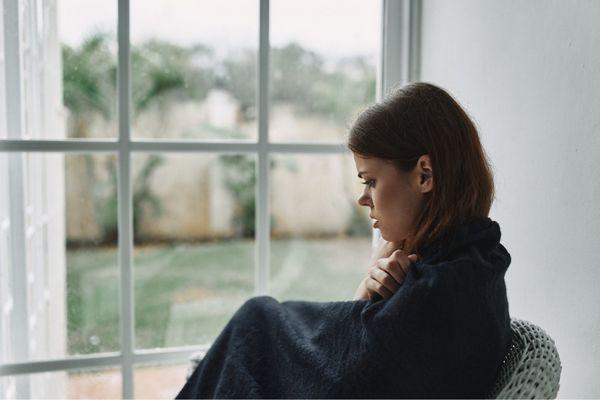 Egy fiatal nő fekete takaróval betakarva ül egy karosszékben, betegen, szomorúan maga elé néz.