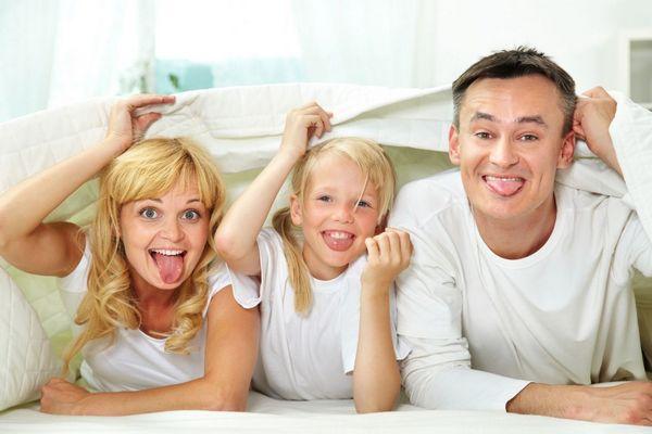Egy család, anya, lány és apa az ágyukon hason fekszenek, nyelvüket kiöltve mosolyognak, kezükkel lepedőt tartanak a fejük felé.
