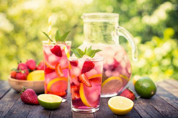 Egy asztalon nyári gyümölcsök, eper, citrom, lime, mellettük üvegkancsóban és üvegpoharakban gyümölcsökből készült limonádé.
