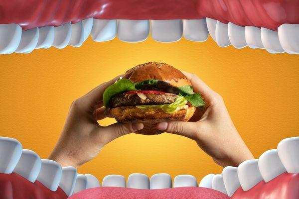 Egy imitált fogsor elé nagy hamburgert tart egy kéz.
