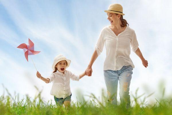 Kint a természetben anya kislányával szalad, szalmakalapot viselnek az erős napsütés miatt.