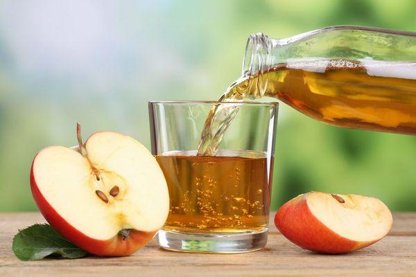 Egy asztalon félbevágott alma, mellette üvegből egy üvegpohárba almalevet öntenek.