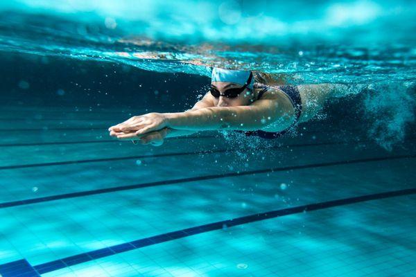 Egy uszodában fiatal nő a víz alatt úszik.