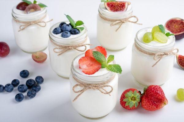 Egy asztalon öt üvegben joghurt, a tetejükön és mellettük gyümölcsök, eper, fekete áfonya, szőlő, füge.
