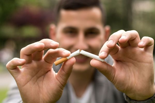 Egy fiatal férfi a két kezében cigarettát tart, amit eltör.