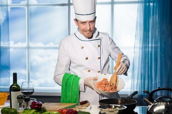 Egy konyhában egy séf főz, egy tálat mutat, amelyben hús van.