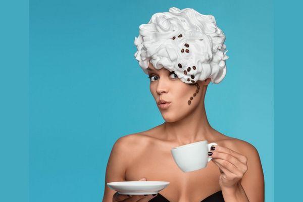 Egy fiatal nő fején a haja helyett kávészemek és tejszínhabot imitáló sapka, kezében kávés csésze.